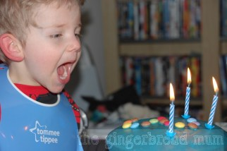 blowing out the candles on his blue chocolate cake